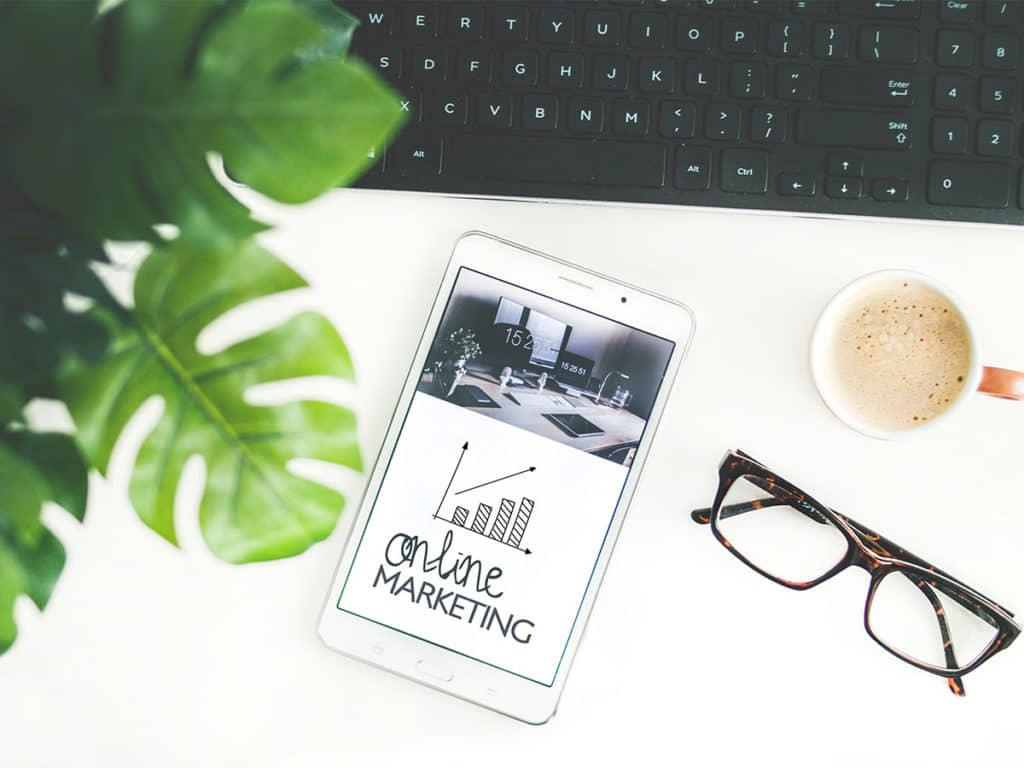 plant met toetsenbord, telefoon met de tekst online marketing en stijgende grafiek, leesbril en koffie
