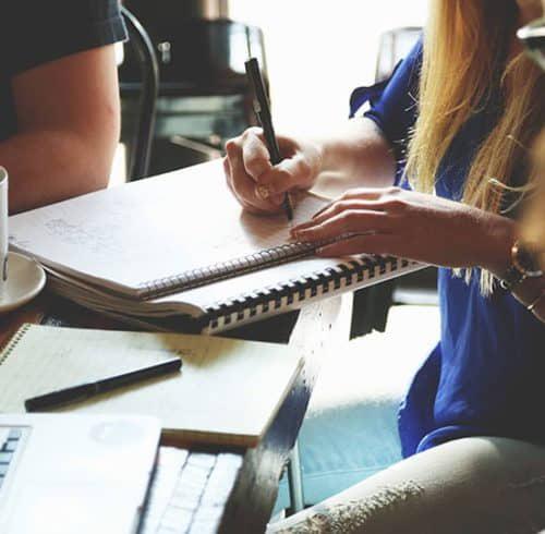 vrouw met potlood in hand en schrijfblok, koffie en een laptop
