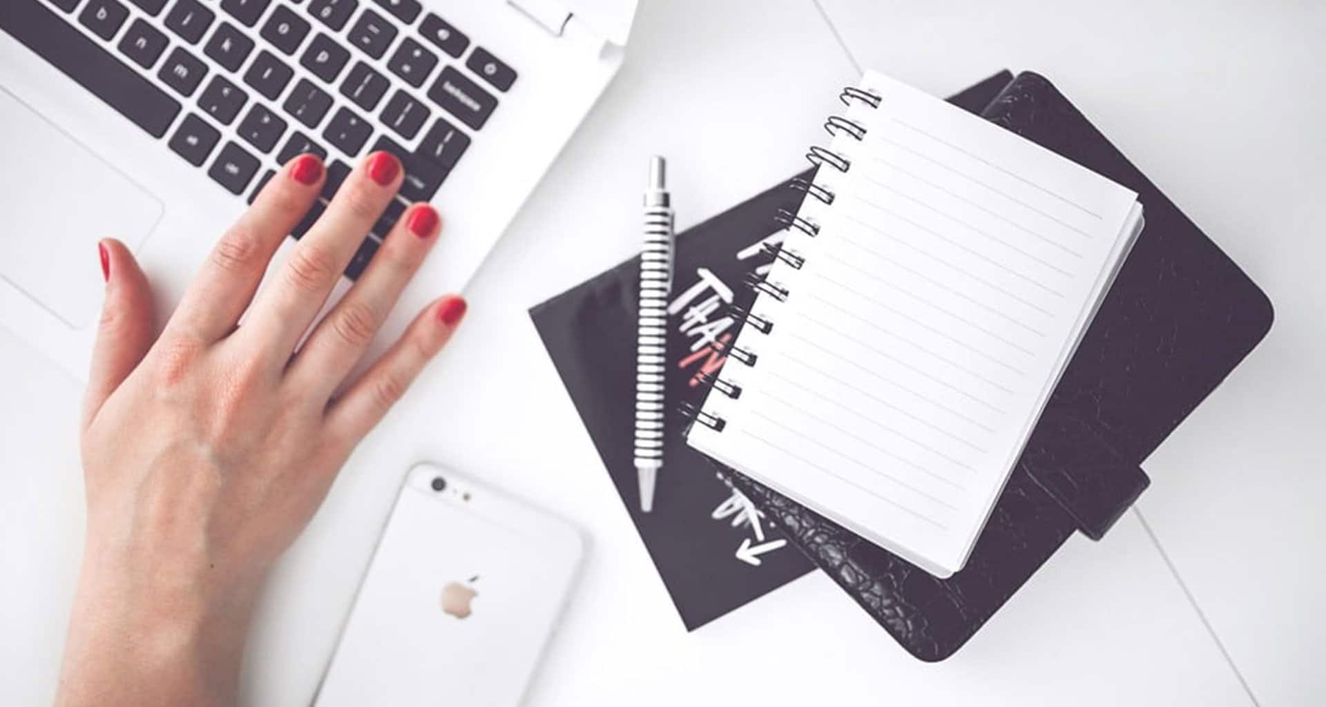 hand met macbook, iphone met een pen en schriften