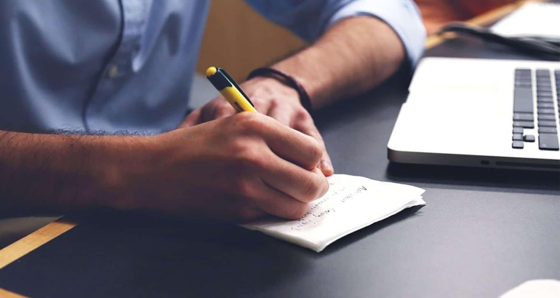 handen met een pen en papier met een macbook