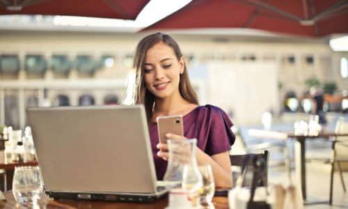 meid met parasol op een terras met laptop en mobiel