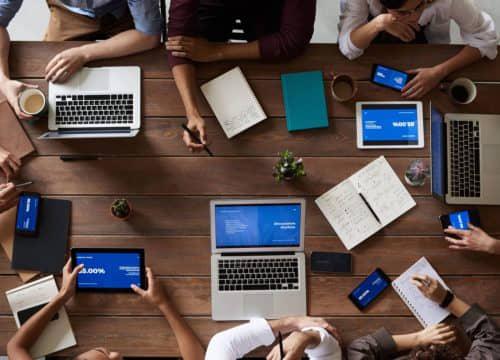 mensen om houten tafel met laptops, tablets en telefoons